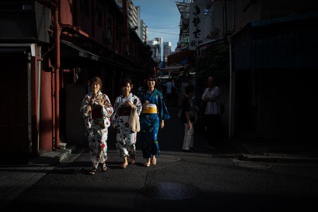 Women wearing kimonos walk along a street in Tokyo's Asakusa district on July 3, 2018. (Photo by Martin Bureau/AFP Photo)