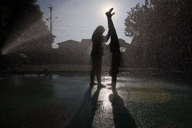 In this January 21, 2015 photo, a girl helps her friend do a handstand in the spray of a water fountain at a park in Santiago, Chile. Kids are cooling off during a heat wave in one of the hottest summers ever in public fountains, forgetting they live in a concrete city. (Photo by Luis Hidalgo/AP Photo)