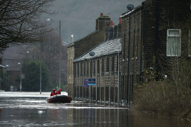 Rescue workers patrol the waters after the River Calder bursts its bank's on December 26, 2015 in Mytholmroyd, England. There are more than 200 flood warnings across Britain as home and business owners prepare for serious flooding. The army has been deployed to some villages to bolster flood defences as rain continues to fall across the north. (Photo by Christopher Furlong/Getty Images)