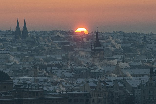 The sun rises over the snow covered rooftops of central Prague on February 12, 2021, as the temperatures dropped to minus 17 degrees Celsius in the Czech capital. (Photo by Michal Cizek/AFP Photo)