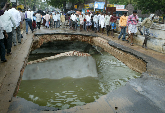 Indian local villagers walk on a bridge damaged by tsunami hit in Nagapattinam town, 350 km (219 miles) south of the southern Indian city of Madras, December 27, 2004. The death toll in a tidal wave triggered by an earthquake that slammed into coasts from India to Indonesia topped 22,000 on Monday as rescuers scoured the sea for missing tourists and soldiers raced to recover bodies amid growing fears of disease. (Photo by Punit Paranjpe/Reuters)