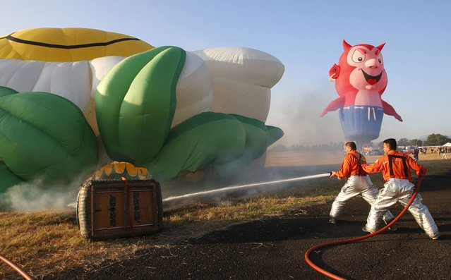 Firemen aim their hose on a hot air balloon that caught fire while being inflated during the Philippine International Hot Air Balloon Fiesta at Clark Freeport Zone in Pampanga province, north of Manila February 12, 2015. (Photo by Erik De Castro/Reuters)