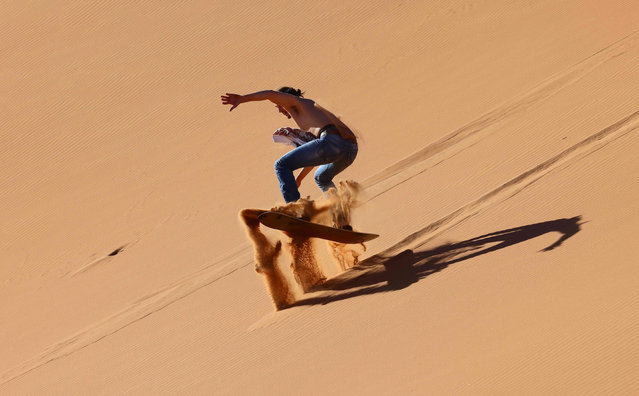 A tourist practises sandboarding in the Dubai desert in the United Arab Emirates, on January 11, 2021. As much of the world tightens lockdowns to stem coronavirus, Dubai has flung its doors open, branding itself as a sunny, quarantine-free escape – despite a sharp rise in cases. (Photo by Giuseppe Cacace/AFP)