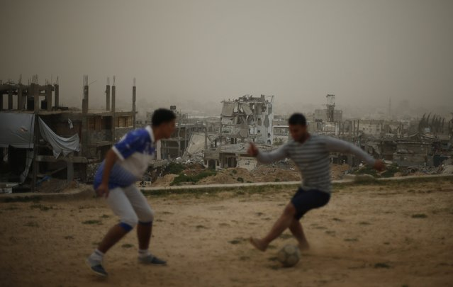 Palestinians play soccer in front of ruined houses, which witnesses said were destroyed by Israeli shelling during a 50-day war last summer, on a stormy day in the east of Gaza City February 10, 2015. (Photo by Mohammed Salem/Reuters)