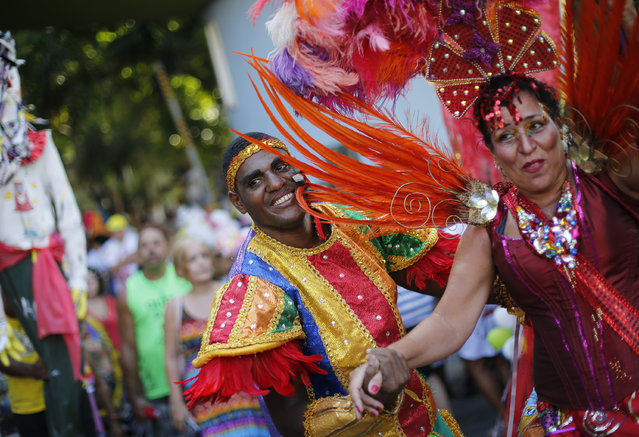 "Patients from the Nise de Silveira mental health institute dance in costume during the institute's carnival parade, coined in Portuguese: ""Loucura Suburbana"", or Suburban Madness, in the streets of Rio de Janeiro, Brazil, Thursday, February 12, 2015. Patients, their relatives and workers from the institute held their parade one day before the official start of Carnival. (Photo by Silvia Izquierdo/AP Photo)"
