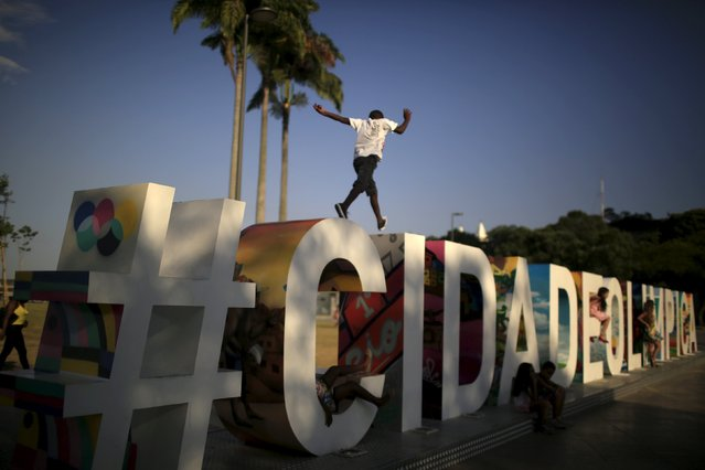 "A boy jumps over big letters that reads ""Olympic City"" at Maua square in the port of Rio de Janeiro, Brazil, January 8, 2016. The Maua square is part of the project Marvelous Port, for the regeneration of Rio's port area. (Photo by Pilar Olivares/Reuters)"