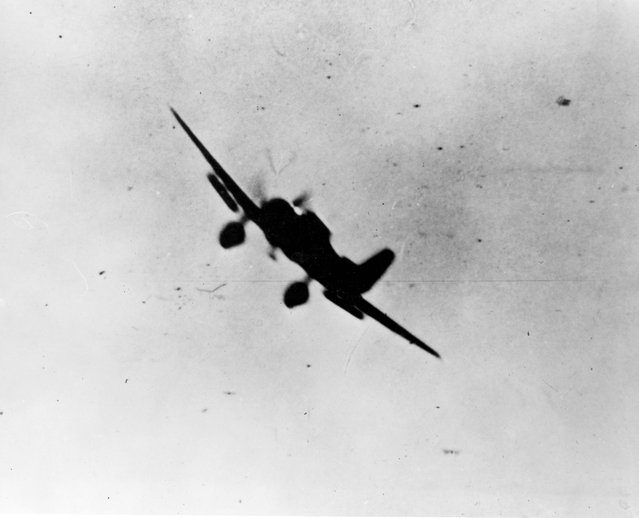 A Japanese Navy Type 99 Val carrier bomber is seen in action during the attack on Pearl Harbor, Hawaii, U.S. December 7, 1941. (Photo by Reuters/U.S. Navy/National Archives)