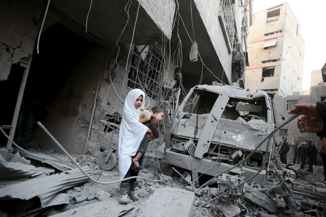 A girl carrying a baby inspects damage in a site hit by what activists said were airstrikes carried out by the Russian air force in the town of Douma, eastern Ghouta in Damascus, Syria January 10, 2016. (Photo by Bassam Khabieh/Reuters)