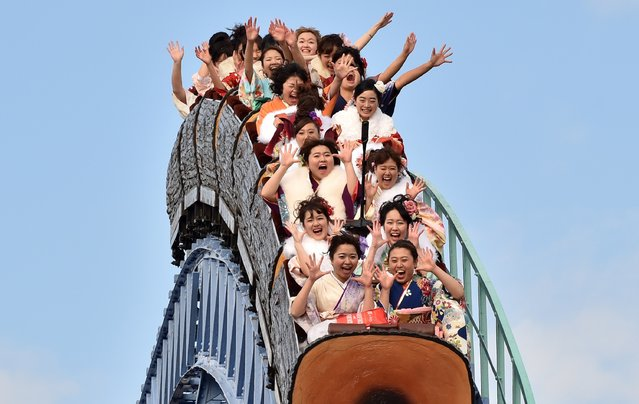 """Twenty-year-old women wearing kimonos ride a rollercoaster after attending a """"Coming-of-Age Day"""" celebration at the Toshimaen amusement park in Tokyo on January 11, 2016. The number of people celebrating """"Coming-of-Age Day"""" in 2016, or adulthood - high by world standards at age 20 - is estimated to stand at 1.21 million, a decrease of 50,000 from the previous year. (Photo by Kazuhiro Nogi/AFP Photo)"""