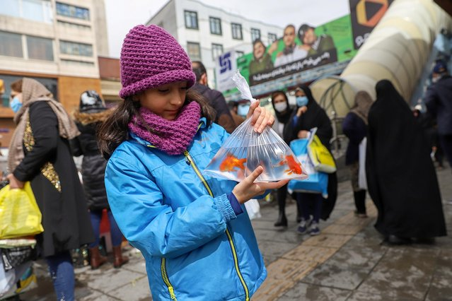 An Iranian girls a bag of goldfish ahead of Nowruz, the Iranian New Year, in Tehran, Iran on March 17, 2021. (Photo by Majid Asgaripour/WANA (West Asia News Agency) via Reuters)
