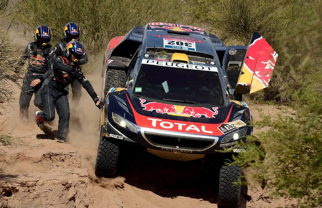 Stephane Peterhansel of France sits in his Peugeot when it starts to slide down, as Peugeot driver Cyril Despres (L, front) of France, Peterhansel's co-pilot Jean Paul Cottret and Despres' co-pilot David Castera try to stop it, during the ninth stage of the Dakar Rally 2016 near Belen, Argentina, January 12, 2016. (Photo by Franck Fife/Reuters)