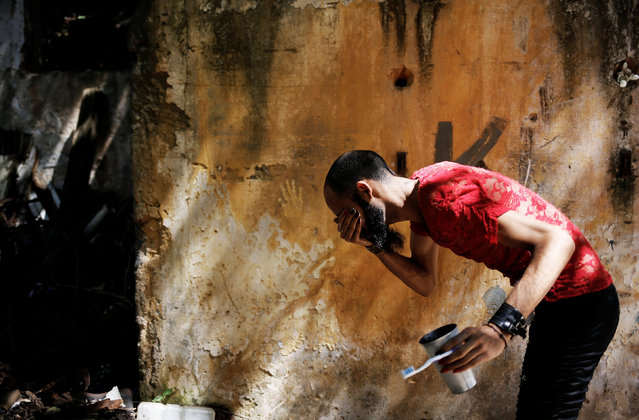 Rodrigo, 26, who is among members of lesbian, gay, bisexual and transgender (LGBT) community, that have been invited to live in a building that the roofless movement has occupied, washes his face, in downtown Sao Paulo, Brazil, November 16, 2016. (Photo by Nacho Doce/Reuters)