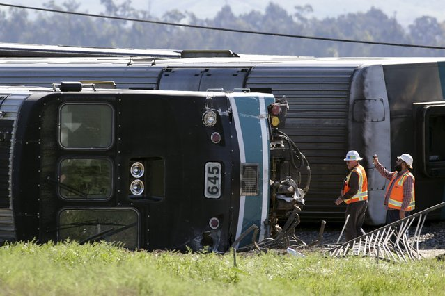 A crew member takes a picture of an overturned passenger car at the scene of a double-decker Metrolink train derailment in Oxnard, California February 24, 2015. A Los Angeles-bound commuter train slammed into a tractor trailer stopped on the tracks in Oxnard, California, during the morning rush hour on Tuesday, injuring more than 30 people, some of them seriously, authorities said. (Photo by Jonathan Alcorn/Reuters)
