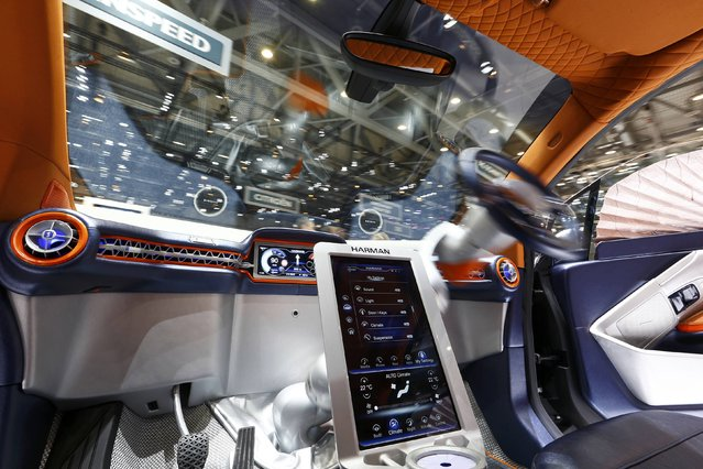 The steering wheel movement is seen inside a Rinspeed Budii self-driving electric city car during the second press day ahead of the 85th International Motor Show in Geneva March 4, 2015. Mounted on a swivelling motorised arm the steering wheel can be used to drive from either side of the car. When not in use the steering wheel rests in the middle of the dashboard.  REUTERS