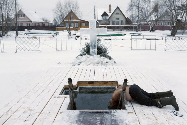 A man dips his head in icy waters during celebrations for the Orthodox Epiphany in the historic town of Pereslavl Zalessky, Russia, January 19, 2016. (Photo by Maxim Zmeyev/Reuters)