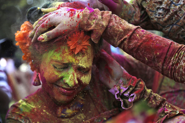FILE - In this Thursday, March 5, 2015 file photo, people smear colored powder on the face of a girl as they celebrate Holi in Kolkata, India. (AP Photo/ Bikas Das, File)
