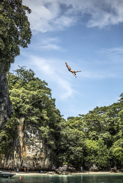 In this handout image provided by Red Bull, Artem Silchenko of Russia dives from the 27 metre platform at training on Hong Island in the Andaman Sea during the final stop of the 2013 Red Bull Cliff Diving World Series on October 25, 2013 at Krabi, Thailand. (Photo by Romina Amato/Red Bull via Getty Images)