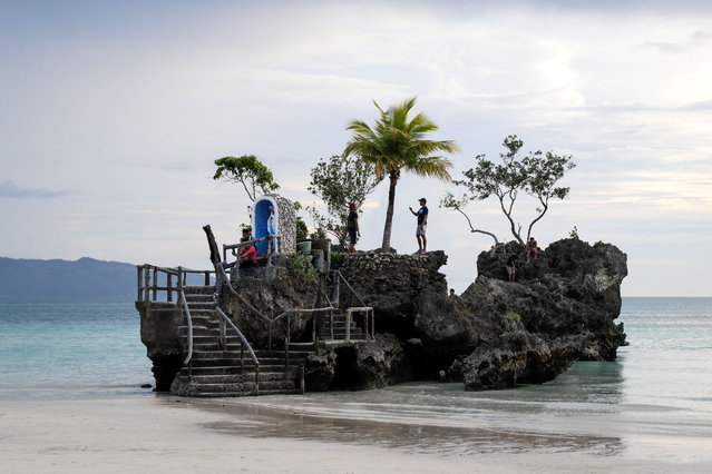 """People pose for pictures on the Boracay Grotto also known as """"Willy's Rock"""" on the island of Boracay, Philippines, 16 October 2018. The island of Boracay has reopened for a """"dry run"""" of ten days after it was closed to the public for six months for sanitation and development work at the tourist destination, which the country's president had called a """"cesspool"""". (Photo by Mark R. Cristino/EPA/EFE)"""