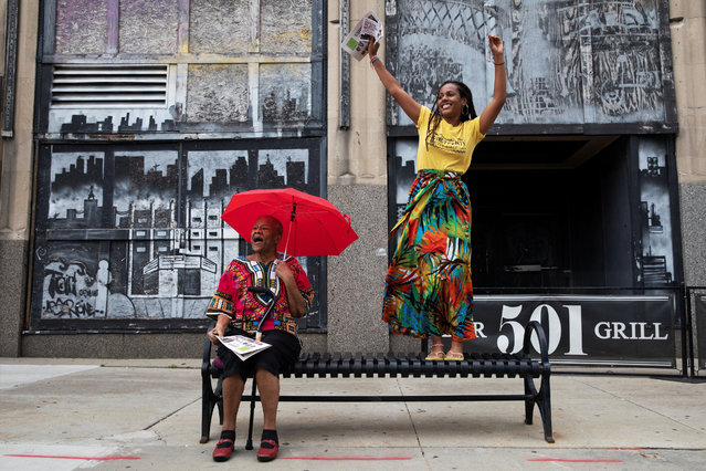 Briana Wilson, 22, dances on a bench as her grandmother, Jean Springer, cheers next to her during a parade to celebrate Juneteenth, which commemorates the end of slavery in Texas, two years after the 1863 Emancipation Proclamation freed slaves elsewhere in the United States, in Flint, Michigan, U.S., June 19, 2021. (Photo by Emily Elconin/Reuters)