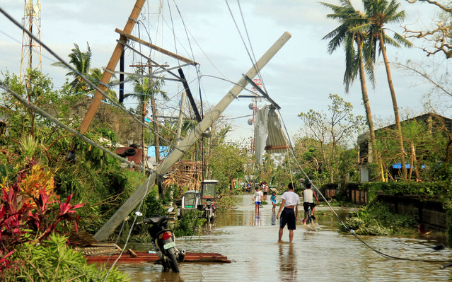 Residents walk past partially toppled electric posts after Typhoon Nock Ten hit Malinao, Albay in central Philippines December 26, 2016. (Photo by Renellyn Loaquinario/Reuters)