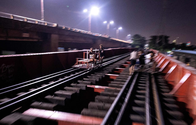 """This picture taken on October 18, 2018 shows a """"trolley boy"""" (C) pushing a home- made cart along a train track in Manila. Scores of commuters in the city of about 12 million are propelled to their destinations daily by so-called """"trolley boys"""" pushing metal carts that ply a few segments of the sprawling capital's railroads. (Photo by Noel Celis/AFP Photo)"""