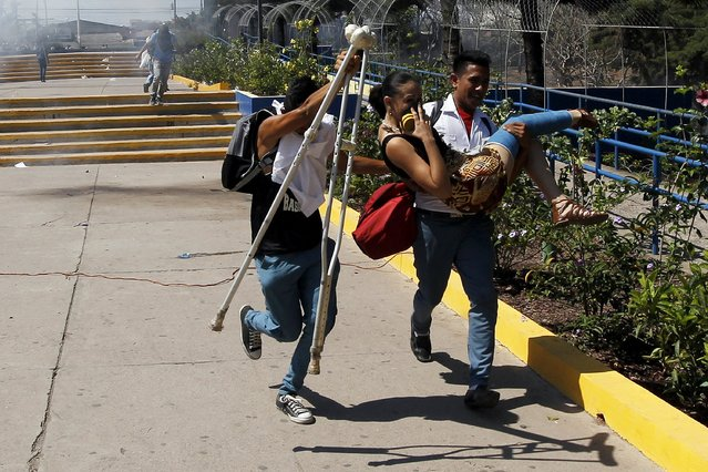 Students help a woman as they run away away from tear gas during a protest in Tegucigalpa March 25, 2015. Students clashed with police during a protest against a change in their class schedule as part of an education reform proposed by the governnment, local media reported. (Photo by Jorge Cabrera/Reuters)