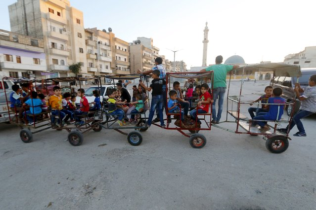 Children play at a makeshift playground during the Muslim festival of Eid-al-Adha in Idlib city, Syria September 24, 2015. (Photo by Ammar Abdullah/Reuters)