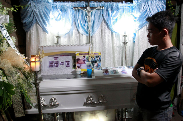 A grieving relative attends the wake of  Angelito, 16, who according to police was killed by unidentified gunmen at a drug den, in Caloocan city, Metro Manila, Philippines December 30, 2016. (Photo by Czar Dancel/Reuters)