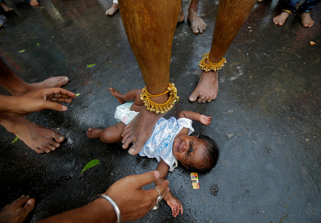 A Hindu holy man touches an infant with his foot as part of a ritual to bless her during a religious procession to mark Bhel Bhel festival dedicated to the Hindu goddess Muthumariamman in Bandel town in the eastern state of West Bengal, India, April 6, 2018. (Photo by Rupak De Chowdhuri/Reuters)