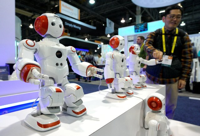A showgoer touches the hand of a robot on display at the Robotics Marketplace at CES in Las Vegas, U.S., January 5, 2017. (Photo by Rick Wilking/Reuters)