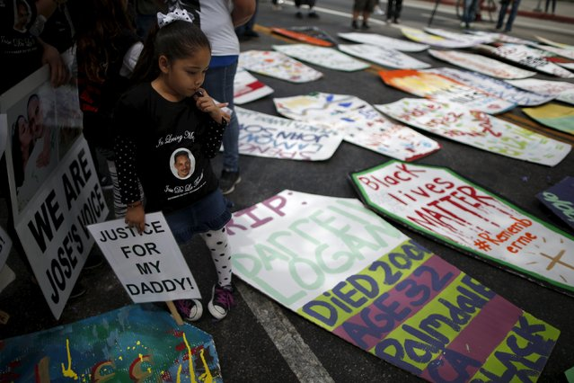 The five-year-old daughter of Jose de la Trinidad, 36, who was fatally shot by Los Angeles County sheriff's deputies, looks at cardboard coffins to commemorate the more than 617 people march organizers say have been killed by law enforcement in LA County since 2000, in Los Angeles, California April 7, 2015. (Photo by Lucy Nicholson/Reuters)