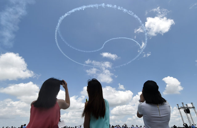 South Korea's Black Eagles aerobatics team performs an aerial display forming a Ying and Yang logo during the Singapore Airshow at Changi exhibition center in Singapore on February 16, 2016. (Photo by Roslan Rahman/AFP Photo)