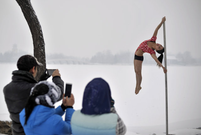 This picture taken on December 17, 2013 shows people taking photos of a pole dancer (R) practising after it snowed in Tianjin during a promotional event by members of China's national pole dancing team and students of the sport. (Photo by AFP Photo)
