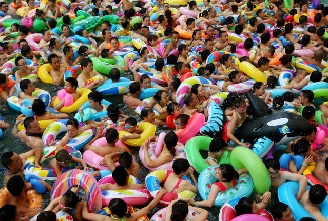 This picture taken on July 27, 2013 shows people trying to cool off at a water park in Suining, southwest China's Sichuan province, as a heatwave hit several provinces in China. (Photo by AFP Photo)