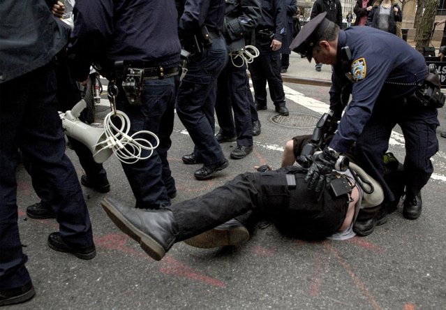 A news photographer is knocked down by a NYPD officer (unseen) as another police officer approaches him during a protest against police brutality against minorities, in New York April 14, 2015. (Photo by Brendan McDermid/Reuters)