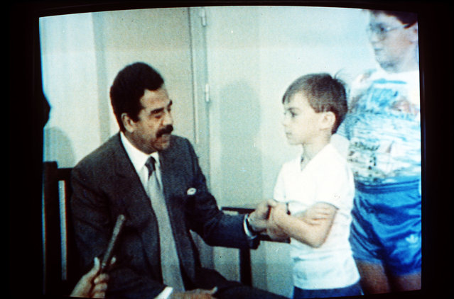 In this undated 1990 file photo, Iraqi President Saddam Hussein, speaks with Western British hostages in an image made from Iraqi TV. (Photo by AP Photo)