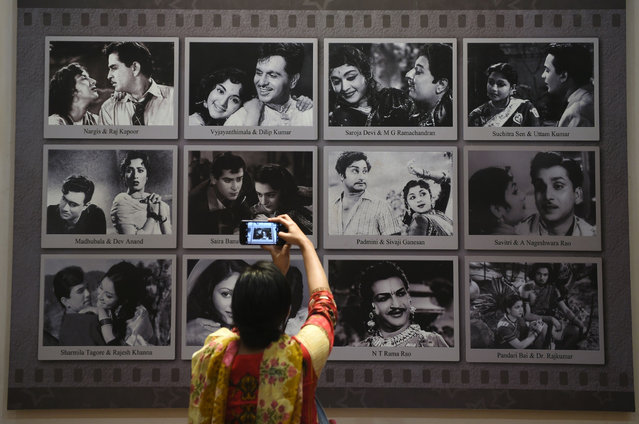 In this picture taken on January 22, 2019, a visitor takes a picture of a display with images of former Indian movie actors at the National Museum of Indian Cinema (NMIC), the country's first museum showcasing the history of its film industry, in Mumbai. From silent black-and-white films to colourful blockbusters bursting with song and dance, a new museum tracing the evolution of Indian cinema has opened in the home of Bollywood. Costing 1.4 billion rupees (19.6 million USD), India's first national film museum is spread across a stylish 19th-century bungalow and a modern five-storey glass structure in south Mumbai. (Photo by Punit Paranjpe/AFP Photo)