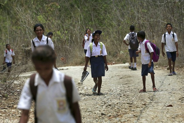 In this October 22, 2018, photo, students walk on dirt road after school in O'of village in West Timor, Indonesia. Children in this impoverished region of Indonesia often must walk long distances to school. Upon graduation, their job opportunities are limited, leaving them with few options beyond a lifetime of subsistence farming in a land punished by drought. (Photo by Tatan Syuflana/AP Photo)