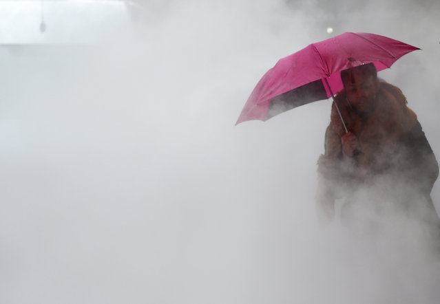 A person walks in the rain and steam coming from a sidewalk grate in Midtown Manhattan in New York January 24, 2017. The city is in the second day of the first Nor'easter of the year with Meteorologists predicting heavy rains with dangerous winds that could gust up to 70 mph, and a risk of flooding in coastal areas. (Photo by Timothy A. Clary/AFP Photo)