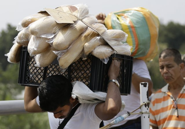 A Venezuelan man carries a crate filled with bread back to his country, in La Parada, on the outskirts of Cucuta, Colombia, on the border with Venezuela, Monday, February 4, 2019. More than a dozen European Union countries endorsed Venezuelan opposition leader Juan Guaido as the county's interim president on Monday, piling the pressure on embattled President Nicolas Maduro to resign and clear the way for a new presidential election. (Photo by Fernando Vergara/AP Photo)