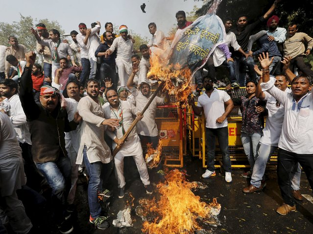 Demonstrators from Indian Youth Congress (IYC) burn an effigy of Indian education minister Smriti Irani during a protest march near the Indian Parliament in New Delhi, India, March 2, 2016. Hundreds of activists gathered to protest and express solidarity for Rohith Vemula, a low-caste student of the University of Hyderabad who was found hanging at a hostel in January this year. (Photo by Anindito Mukherjee/Reuters)