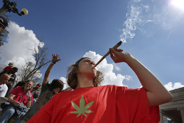 Partygoers listen to music and smoke marijuana on one of several days of the annual 4/20 marijuana festival, in Denver's downtown Civic Center Park, Saturday April 18, 2015. The annual event is the second 4/20 marijuana celebration since retail marijuana stores began selling in January 2014. (Photo by Brennan Linsley/AP Photo)