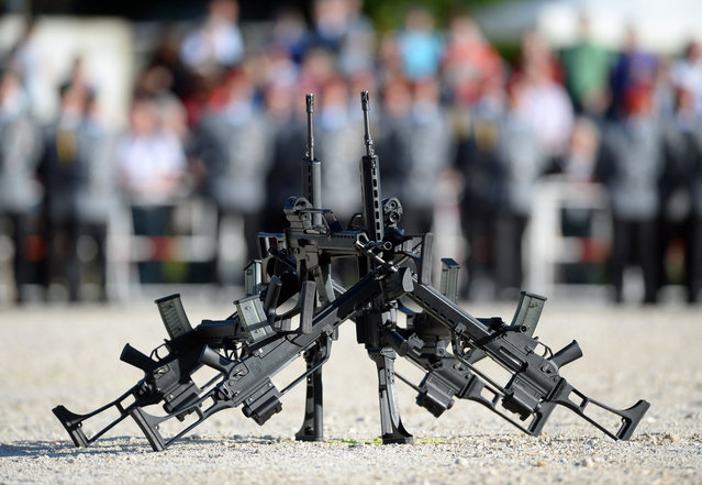 """In this June 5, 2014 file photo G36 rifles of manufacturer Heckler&Koch stand in front of soldiers in Sigmaringen, southern Germany. The widely used assault rifle has """"no future"""" with the German military in its current form, Germany's defense minister Ursula von der Leyen said Wednesday, April 22, 2015, escalating a dispute over the weapon's alleged shortcomings. (Photo by Patrick Seeger/AP Photo/DPA)"""