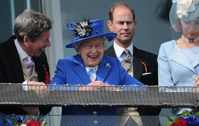 Britain's Queen Elizabeth II (C) standing next to Prince Edward, Earl of Wessex (2R) smiles from the royal balcony as she looks down on the winning horse in the Derby race on Derby Day, the second day of the Epsom Derby horse racing festival, at Epsom in Surrey, southern England, on June 2, 2012 the first official day of Britain's Queen Elizabeth II's Diamond Jubilee celebrations. (Photo by Carl Court/AFP Photo)