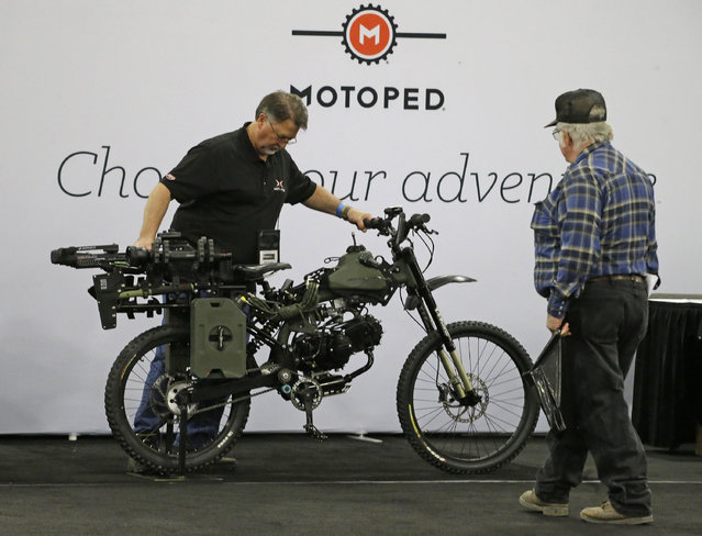 Ken Stone, left, with Motoped, demonstrates the Motoped Survival Bike during the PrepperCon expo Friday, April 24, 2015, in Sandy, Utah. (Photo by Rick Bowmer/AP Photo)