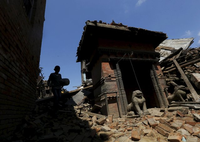 A boy carrying a bolster walks past a damaged temple after Saturday's earthquake in Bhaktapur, Nepal April 27, 2015. (Photo by Adnan Abidi/Reuters)