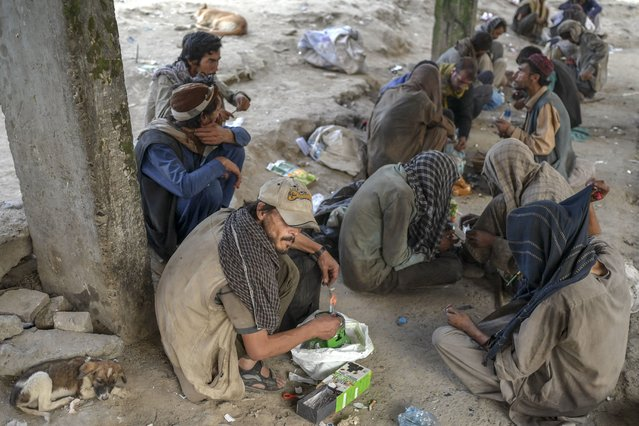 Drug addicts sit on the side of a road as they consume drugs in Kabul on September 21, 2021. (Photo by Bulent Kilic/AFP Photo)