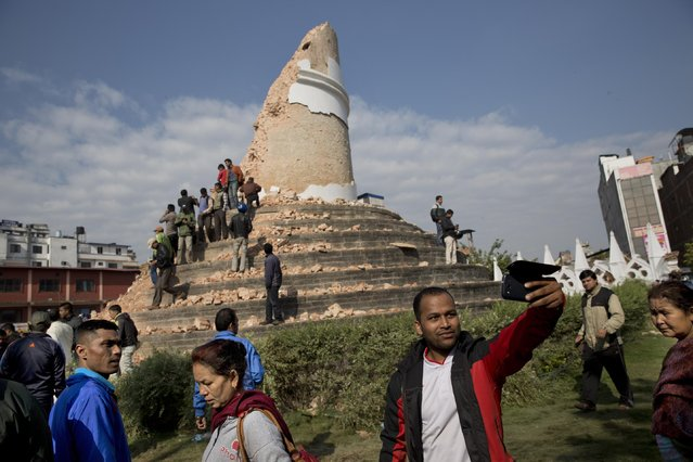 A man takes a selfie at the historic Dharahara Tower, a city landmark, that was damaged in Saturday's earthquake in Kathmandu, Nepal, Monday, April 27, 2015. A strong magnitude earthquake shook Nepal's capital and the densely populated Kathmandu valley on Saturday devastating the region and leaving tens of thousands shell-shocked and sleeping in streets. (Photo by Bernat Armangue/AP Photo)