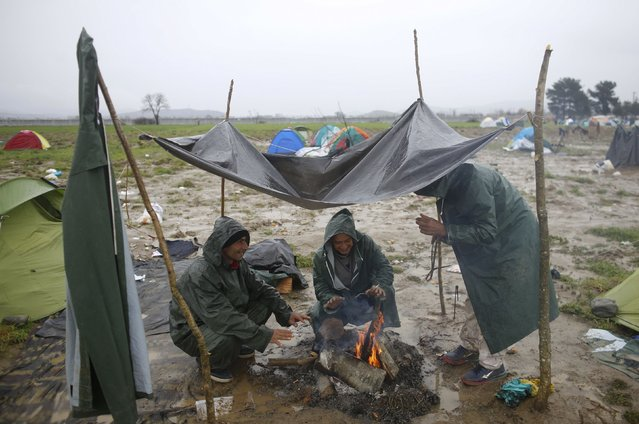 Migrants from Syria warm themselves by fire at a makeshift camp on the Greek-Macedonian border, near the village of Idomeni, Greece March 10, 2016. (Photo by Stoyan Nenov/Reuters)