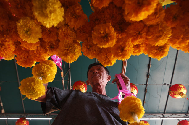 In this Wednesday, January 30, 2019, photo, ethnic Chinese-Thai offers flowers after prayers at the Leng Nuei Yee Chinese temple for the upcoming Lunar New Year in Bangkok, Thailand. (Photo by Sakchai Lalit/AP Photo)